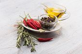 foto of bay leaf  - Fresh hot chili peppers black peppers rosemary oil bay leaves om white wooden background - JPG