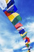 tibetan flags with mantra on sky background