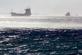 stock photo of mph  - Container ships in the gulf of Trieste while a strong wind known as bora is blowing at 70 mph - JPG