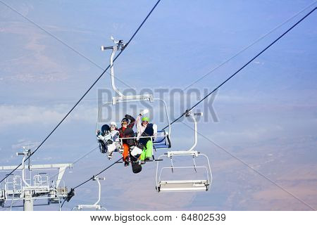 Three snowboarders sitting on ropeway