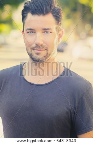 Casual outdoor portrait of a masculine handsome male model with subtle vintage retro styling