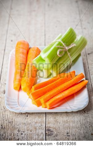 bundle of fresh green celery stems and carrot in plate on wooden background
