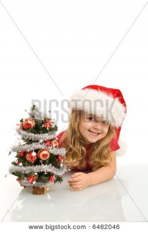 Smiling Little Girl Peeking Out A Small Christmas Tree