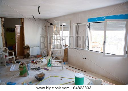 House indoor improvements in a messy room construction with plaste tools and ladder