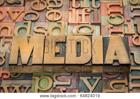 media word in wood type against background of letterpress printing blocks