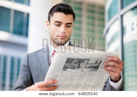 Portrait of a young business man reading a newspaper