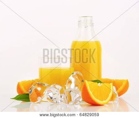 fresh citrus juice poured in the glass and bottle, surrounded with frozen ice cubes