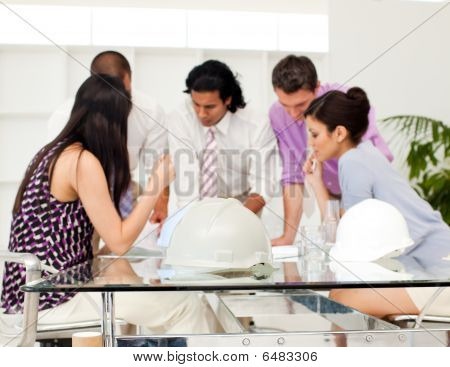 International Architect Co-workers Reviewing Blueprints