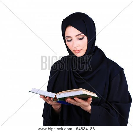Beautiful muslim arabic woman reading book on grey background