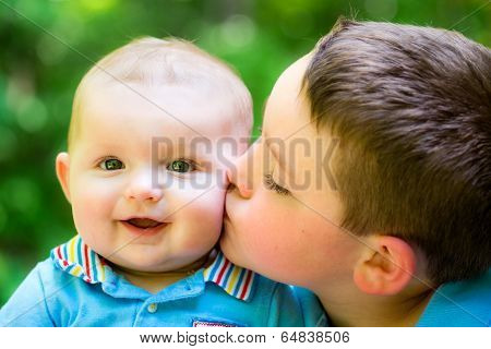 Happy Baby Boy Kissed By His Older Brother