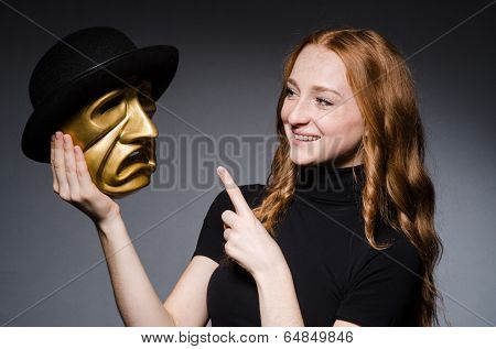Redhead woman with mask in hypocrisy consept against grey background