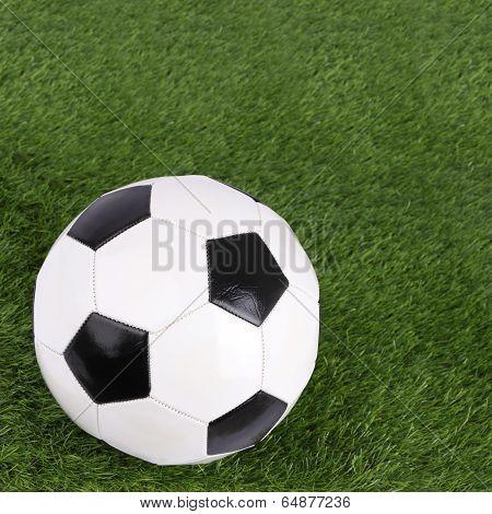 Stitch leather soccer focus ball on blur far green grass field.