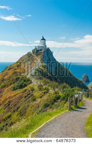 Lighthouse on Nugget Point. It is located in the Catlins area on the Southern Coast of New Zealand, Otago region. The Lighthouse is surrounded by small rock islands, nuggets