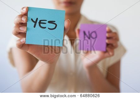 Casual businesswoman showing yes card in her office