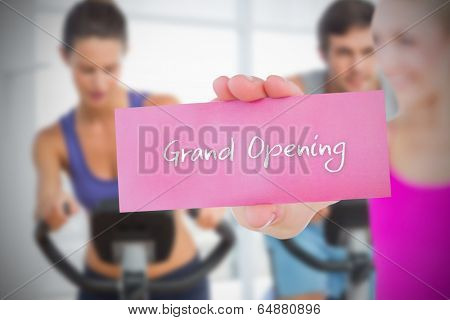Fit blonde holding card saying grand opening against fitness class in gym