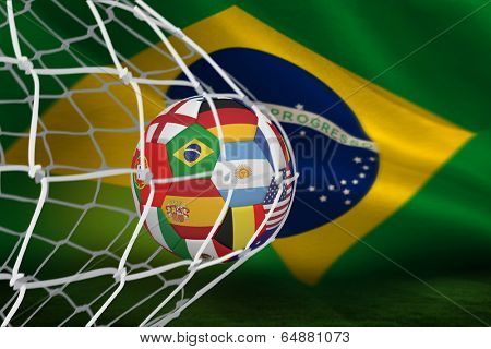 Football in multi national colours at back of net against brazilian flag waving