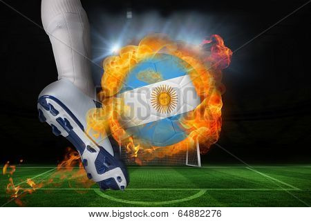 Football player kicking flaming argentina flag ball against football pitch and goal under spotlights