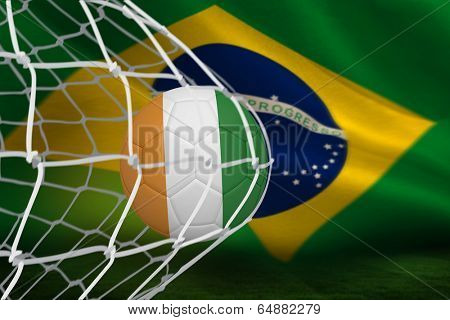 Football in ivory Coast colours at back of net against brazilian flag waving
