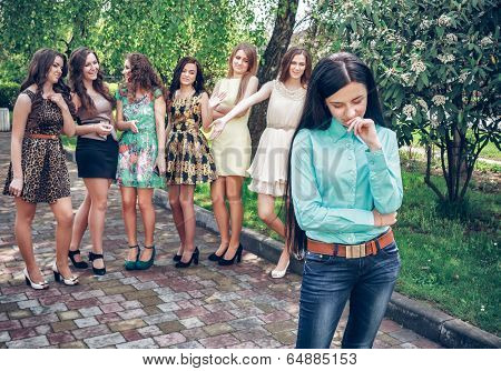 Upset teenage girl with friends gossiping