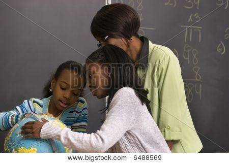 Studenten und Lehrer suchen den Globus im Klassenzimmer