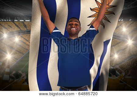 Cheering football fan in blue jersey holding urugauy flag against vast football stadium with fans in yellow