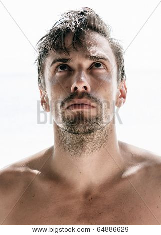 Frontal view of the portrait of a young caucasian handsome man, shirtless and unshaven, with rebel hair, looking up, on white background