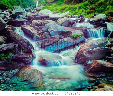 Vintage retro effect filtered hipster style travel image of cascade of Bhagsu waterfall in Himalayas. Bhagsu, Himachal Pradesh, India. Polarizer filter used