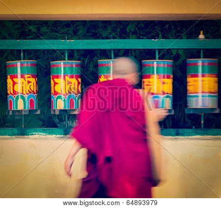 Vintage retro effect filtered hipster style travel image of Buddhist monk passing and rotating prayer wheels on kora around Tsuglagkhang complex in McLeod Ganj, Himachal Pradesh, India