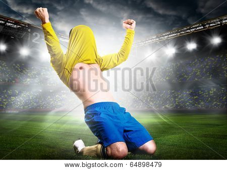 soccer or football player is celebrating goal on stadium with his jersey on head