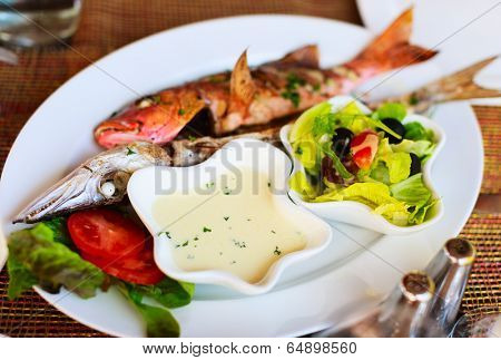 Grilled fish barracuda, green salad and vegetables