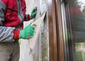 foto of putty  - Plasterer spreading out plaster with trowel around the windows - JPG
