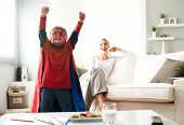 stock photo of playtime  - Superhero boy having an healthy snack with cookies and milk with his mother on background - JPG