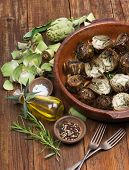 stock photo of artichoke hearts  - roasted and fresh artichokes with olive oil pepper and salt on the wooden table - JPG
