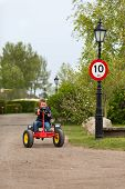 stock photo of mph  - Boy driving pedal go cart next to 10 MPH speed limit sign - JPG
