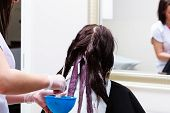 stock photo of hair dye  - Professional female hairdresser applying color to female customer at design hair salon woman having her hair dyed Hair dye colouring in process - JPG