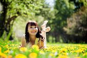 stock photo of harmony  - Young beautiful woman lying on grass full of spring flowers - JPG
