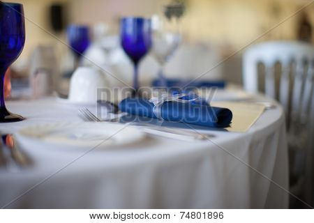Blue serviette detail on a formal wedding table set with blue and white linen and elegant matching glassware, selective focus with the napkin centered and copyspace