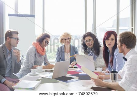 Business colleagues discussing over photographs at conference table in creative office