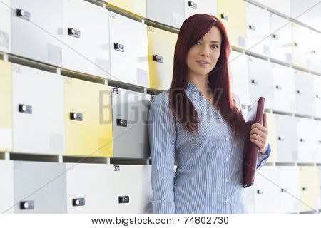 Portrait of beautiful businesswoman with file standing in locker room at creative office