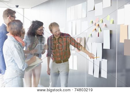Young businessman explaining document to colleagues in creative office