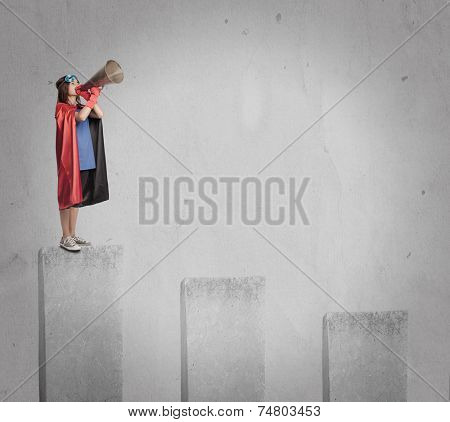 little girl wearing a superhero costume shouting with an old megaphone on the top of a chart