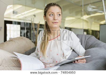 Young businesswoman with tablet PC and book looking away in office