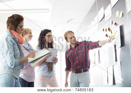 Young businessman explaining document to female colleagues in creative office