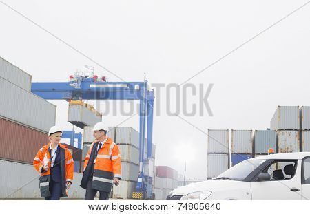 Workers conversing while walking in shipping yard