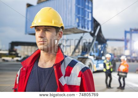 Confident male worker with colleagues in background at shipping yard