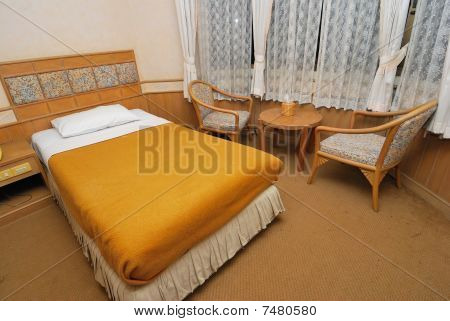 Single Bed In Modern Hotel Room With Table And Chairs