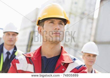 Confident male worker with colleague in background at shipping yard