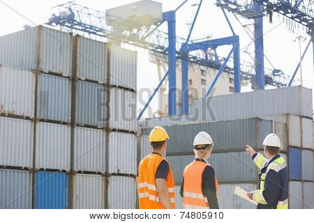 Rear view of workers inspecting cargo containers in shipping yard