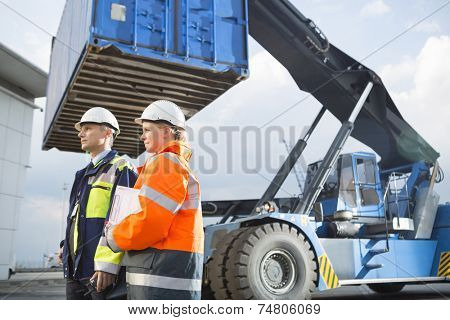 Male and female workers standing by freight vehicle in shipping yard