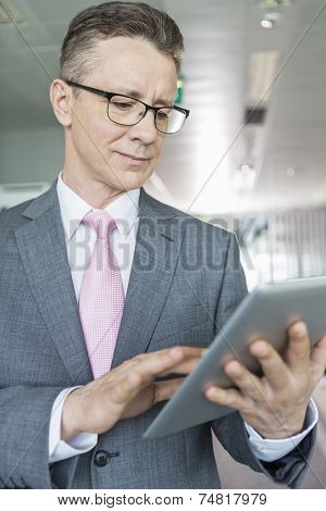 Middle-aged businessman using tablet PC in office